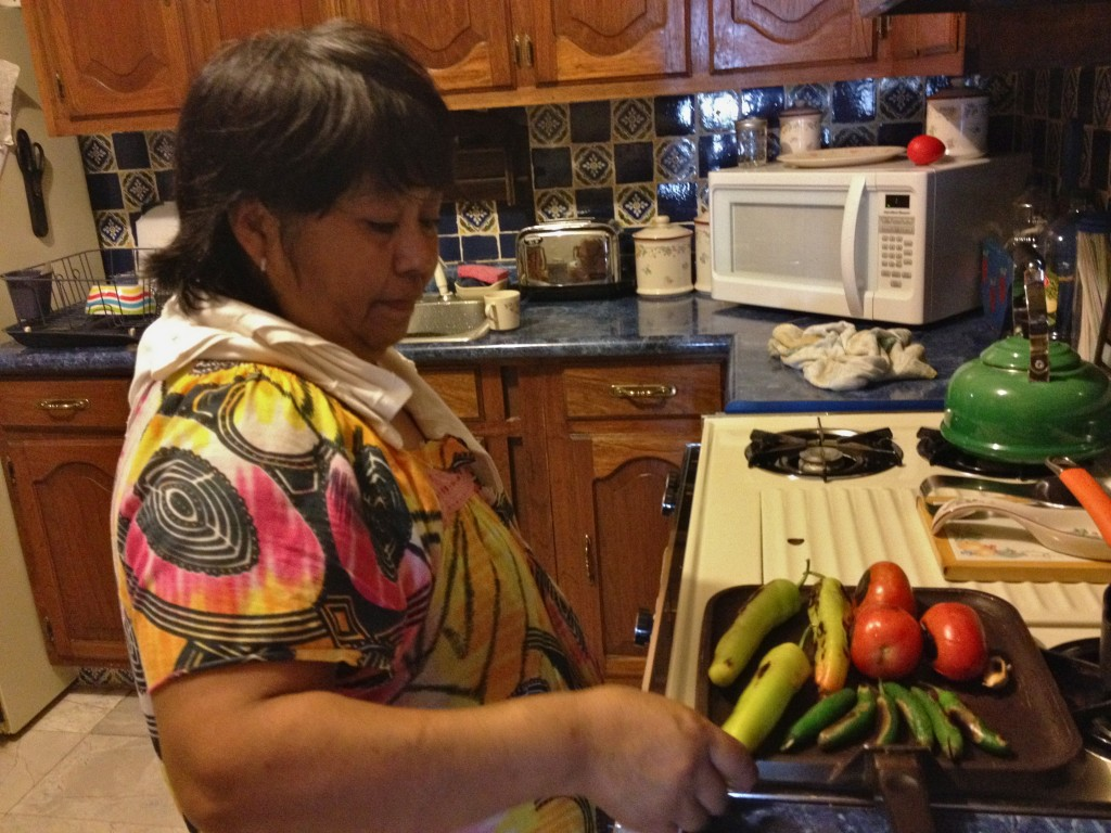 Woman in kitchen roasting vegetables on pan