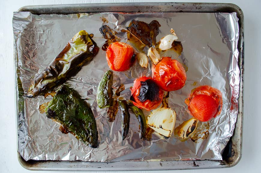 Charred tomatoes, peppers, and onion in a sheet tray lined with foil.