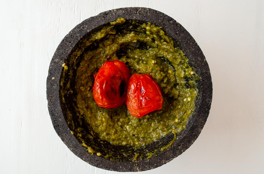 Two tomatoes on top of chile puree in the molcajete