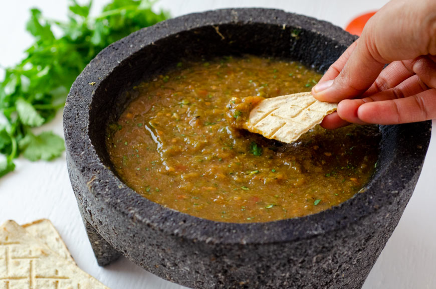 Salsa molcajeteada in a large molcajete surrounded by tomatoes, cilantro, and garlic