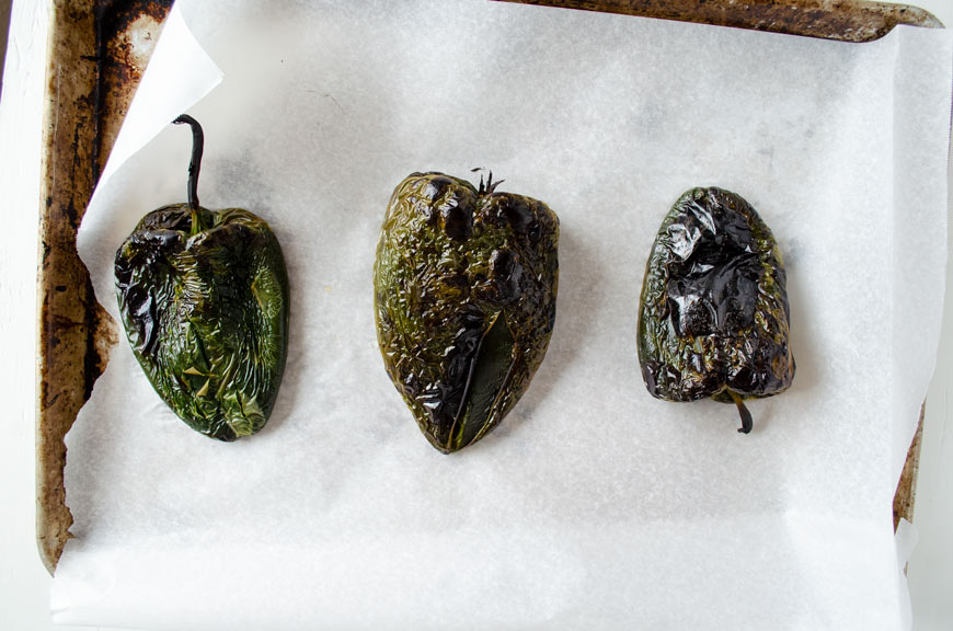 roasted poblano peppers on a sheet tray with parchment paper
