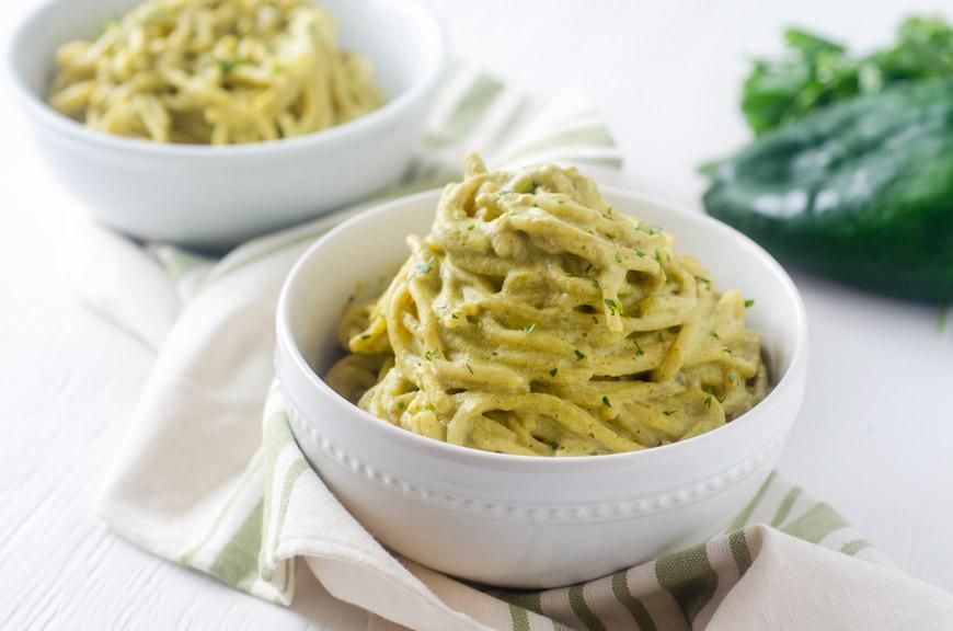 spaghetti on green poblano sauce in a white bowl
