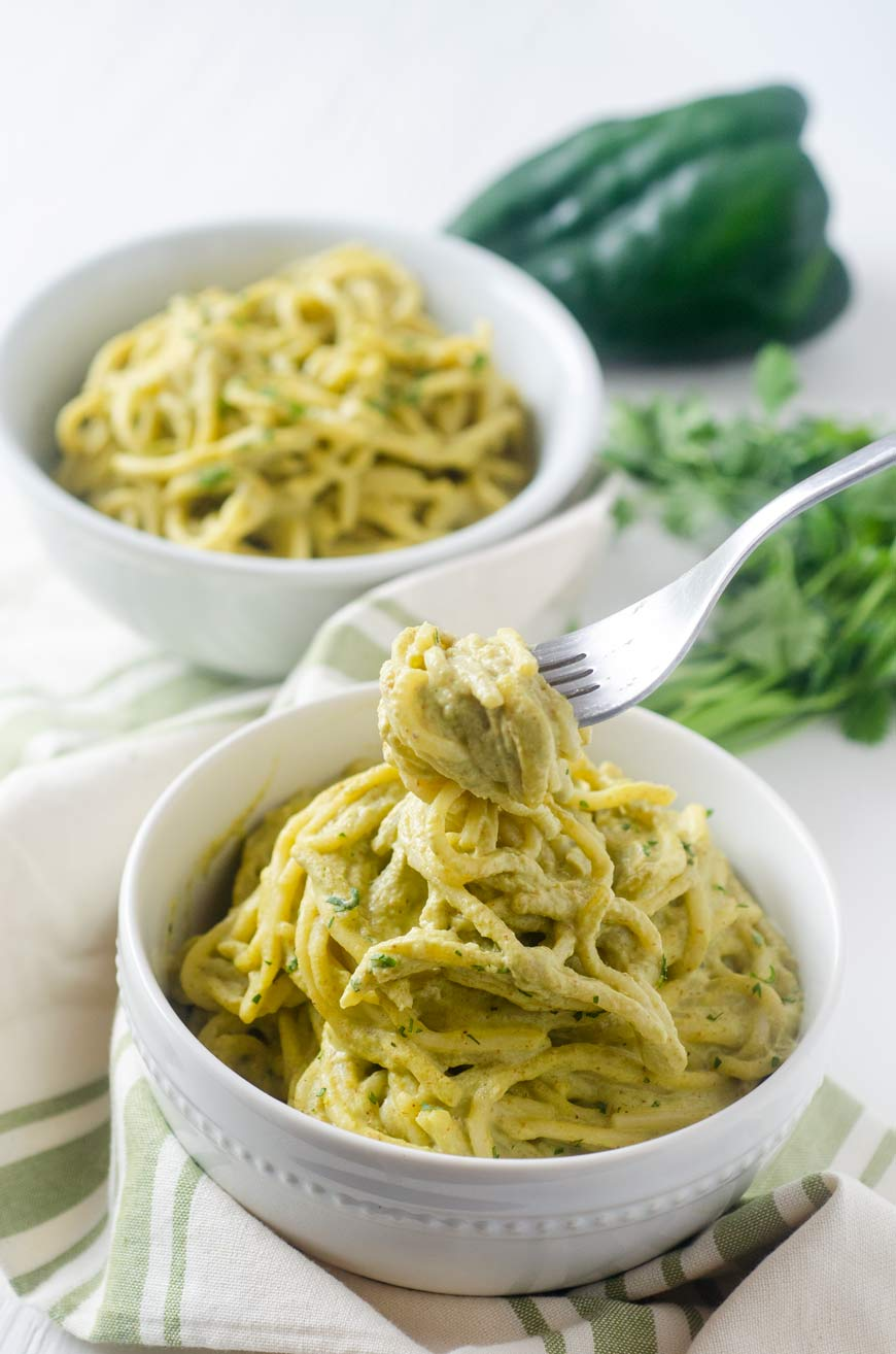 spaghetti on green poblano sauce in a white bowl