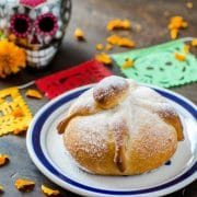 vegan pan de muerto on a wood surface with colorful paper
