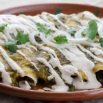 Vegan roasted tomatillo enchiladas, filled with sautéed onions, garlic, poblano peppers, and pinto beans. Bathed in salsa and almond crema.