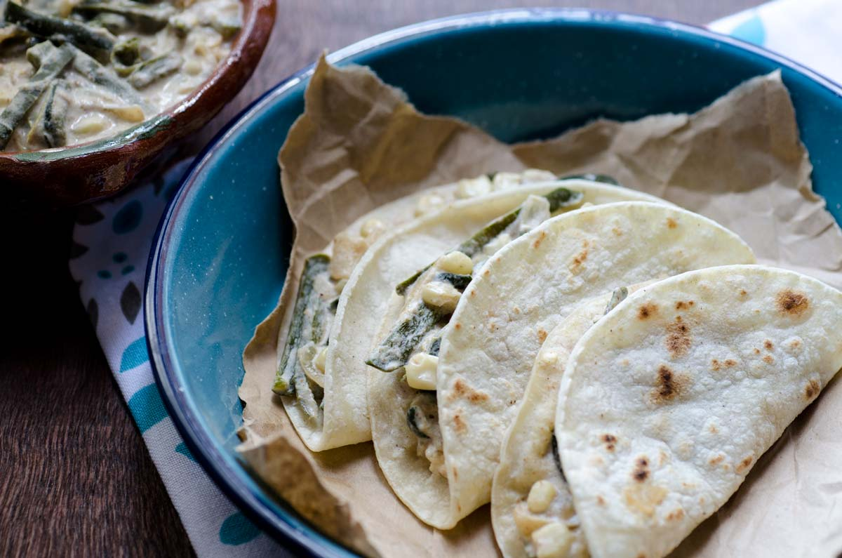 "Vegan Rajas con Crema Tacos is one of those true Mexican comfort dishes. Poblano peppers are roasted over an open flame, peeled, cut into strips, then sauted with onion, garlic, and corn. A thick, slightly sour ""crema"" is poured over the whole thing. It is spicy, creamy, and incredibly satisfying"