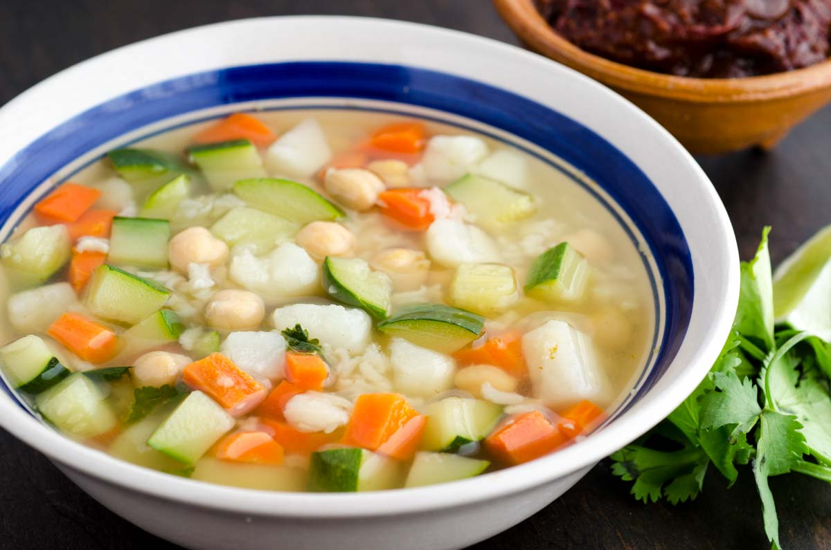 Close up of white bowl with blue rim filled with soup zucchini, carrots, chickpeas and rice
