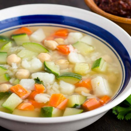 White bowl with blue rim filled with soup zucchini, carrots, chickpeas and rice