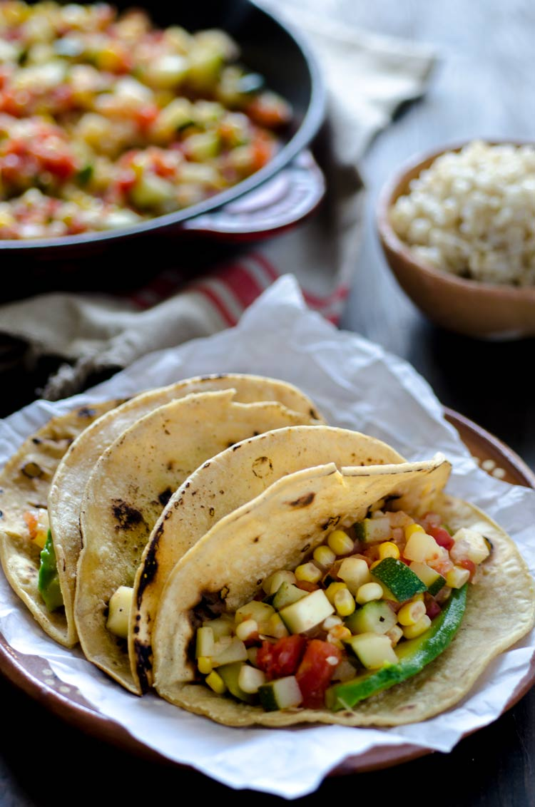 Calabacitas tacos are tender zucchini, ripe tomatoes, sweet corn, and garlic stewed together to make a satisfying, finger licking taco.