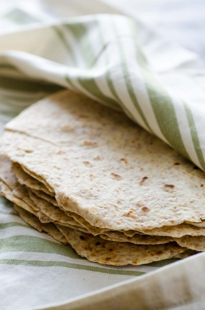 a stack of whole wheat tortillas on a white linen towel with green stripes