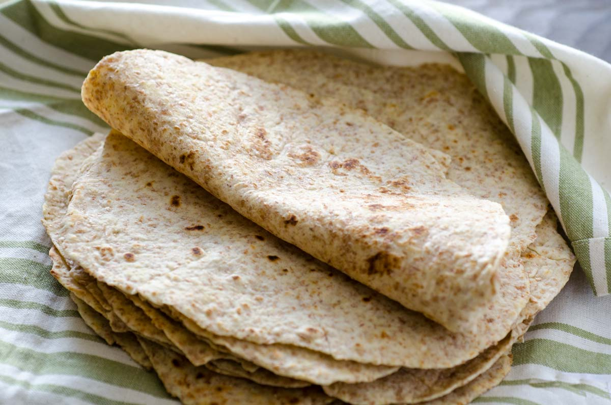 a stack of whole wheat tortillas on a white linen towel with green stripes, with the top tortilla folded over