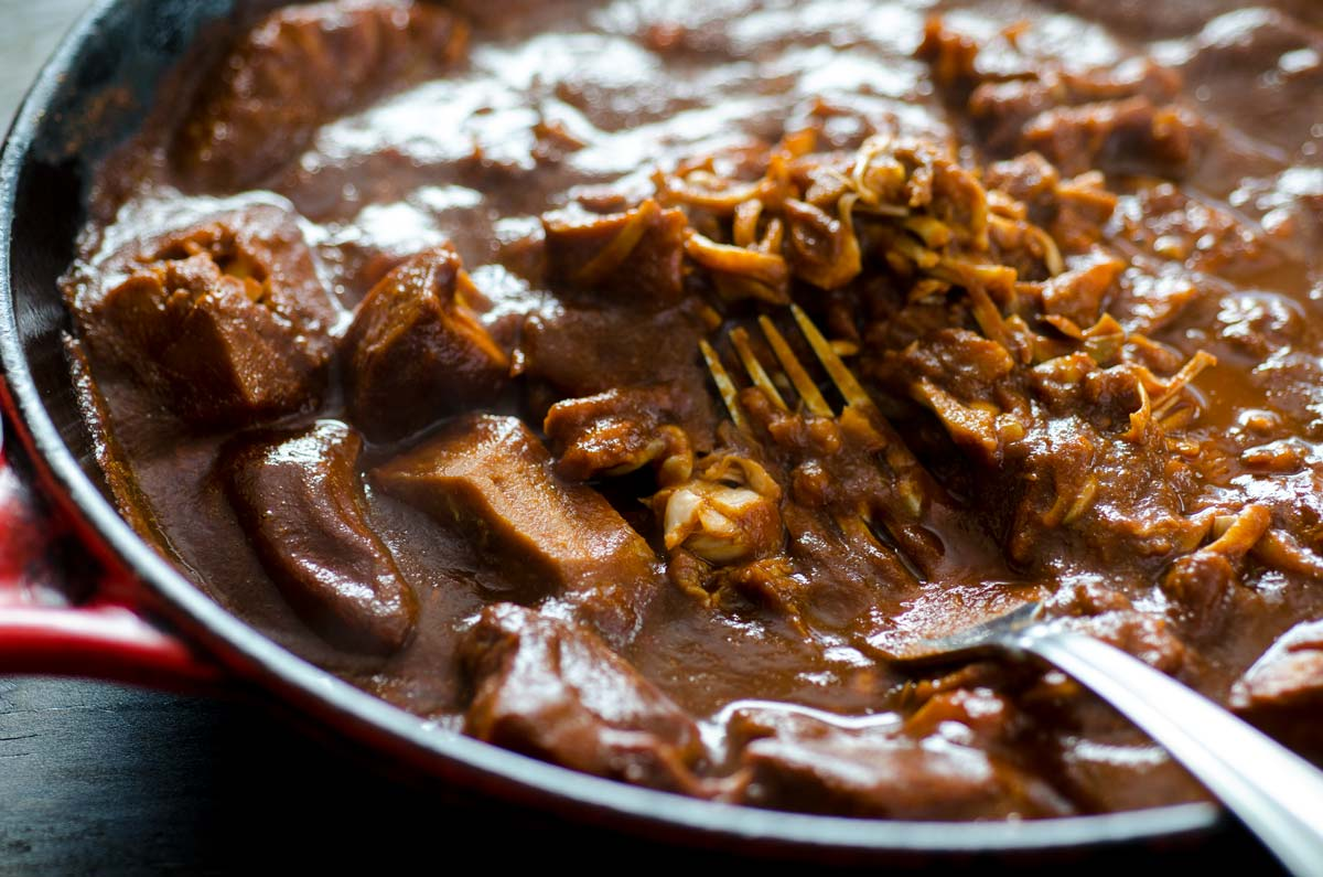 Jackfruit simmering in red chile sauce in a cast iron pan