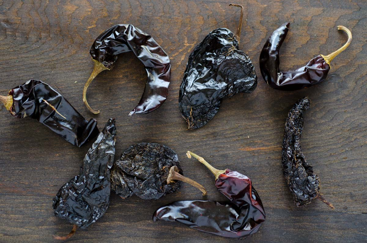 Chile guajillo and chile ancho on a dark wooden surface