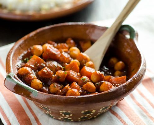 Close up of Sweet potato and chickpea stew in a clay Mexican pot on top of a red and white striped napkin with a wooden spoon showing a bite. Rice in the background