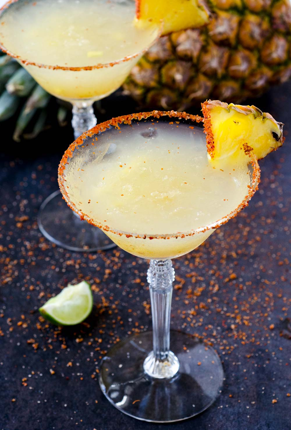 This pineapple chile margarita on the rocks is refreshing, slightly sweet, tart, and a bit spicy. It's hard to have just one!