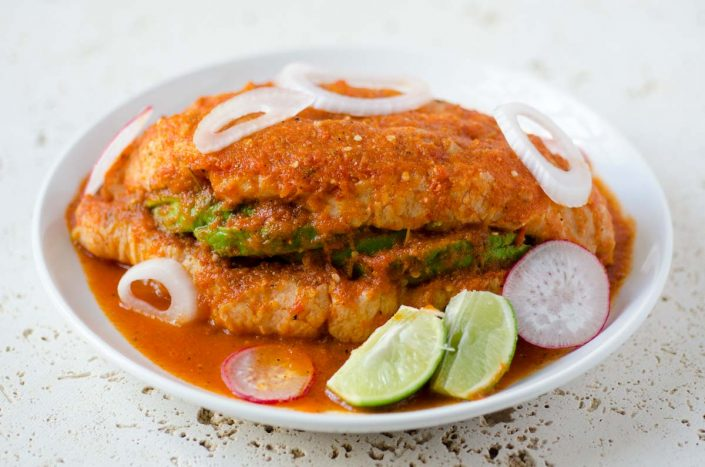 This Torta ahogada recipe is a crusty bread torta filled with refried beans and avocado, and drowned in a spicy chile de arbol salsa.