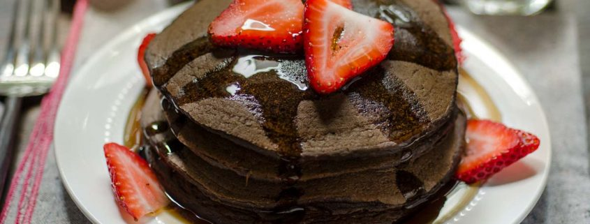 Fluffy and rich vegan chocolate strawberry pancakes for breakfast? Stuffed with thinly sliced strawberries and drizzled with maple syrup!!