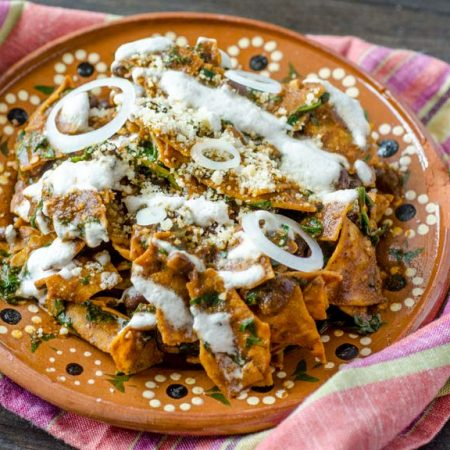 Vegan mole chilaquiles are tortilla chips covered in mole sauce and mixed with sautéed greens and black beans, then drizzled with an almond crema, and vegan queso cotija. The combination is seriously good.