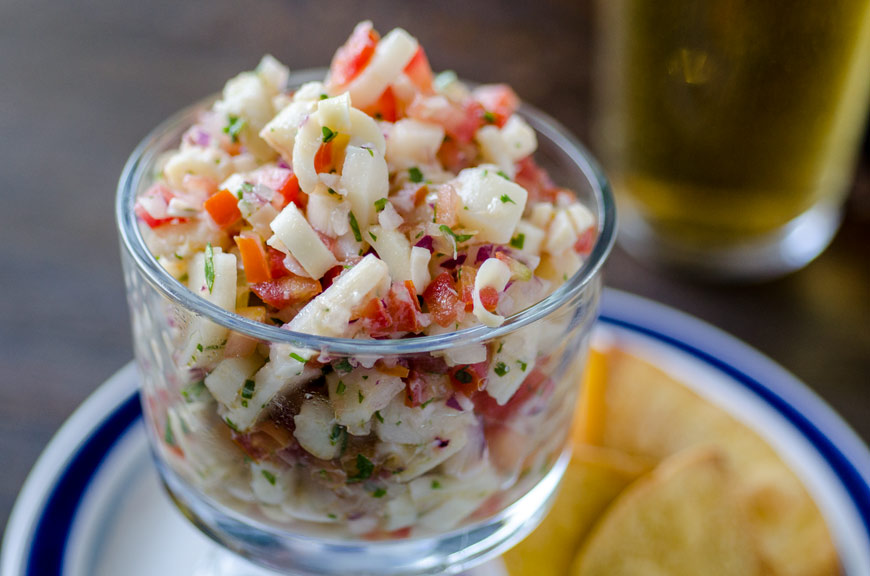 Hearts of palm ceviche on a blue plate with chips, and a beer.
