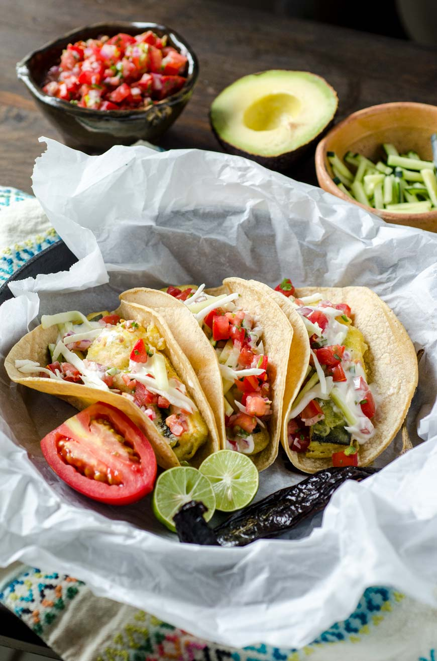 Vegan fish tacos in a cast iron pan with limes, tomato, and avocado