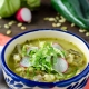 Vegan pozole verde topped with lettuce, radishes, and avocado in a blue and white talavera bowl
