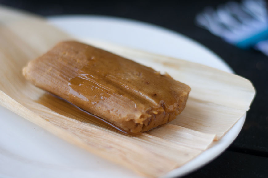 Pumpkin pie tamal bathed in syrup on a white plate