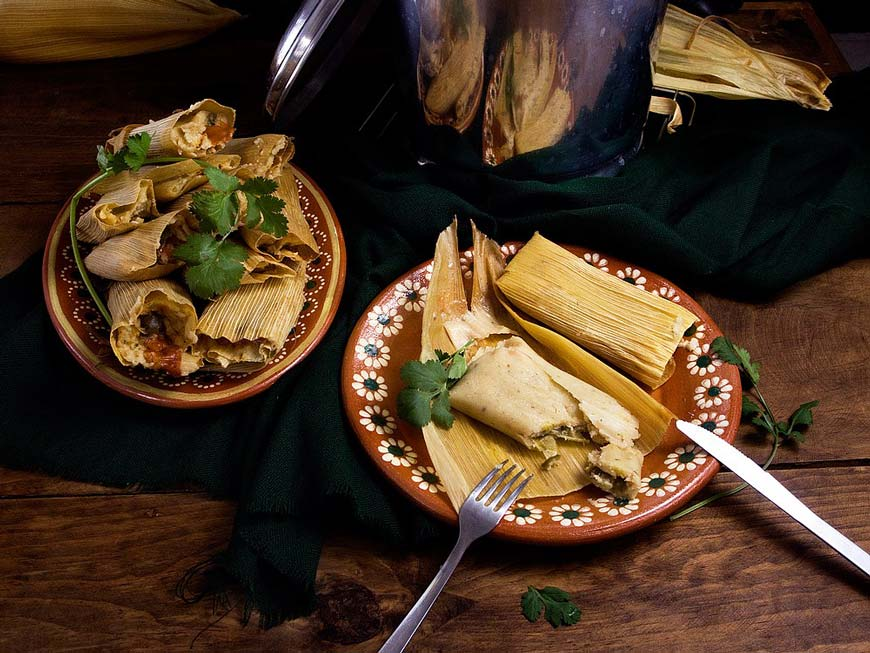 Tamales on Mexican clay plates on a dark background
