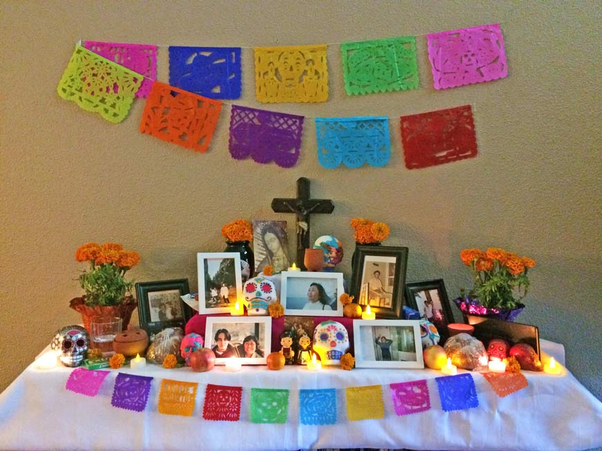 Altar de muertos, a table with pictures, candles, bread, a cross