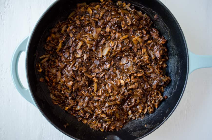 Mushroom in mole sauce in a large saute pan for vegan empanadas