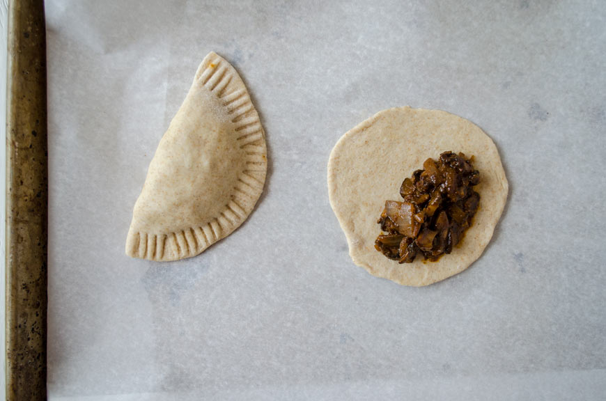 vegan empanada dough rolled out and filled with mushrooms in mole