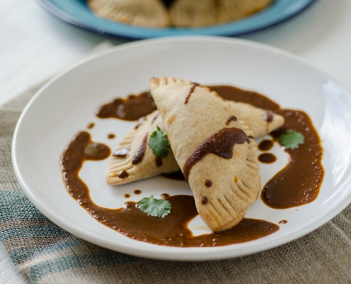 vegan empanadas on a white plate with mole sauce