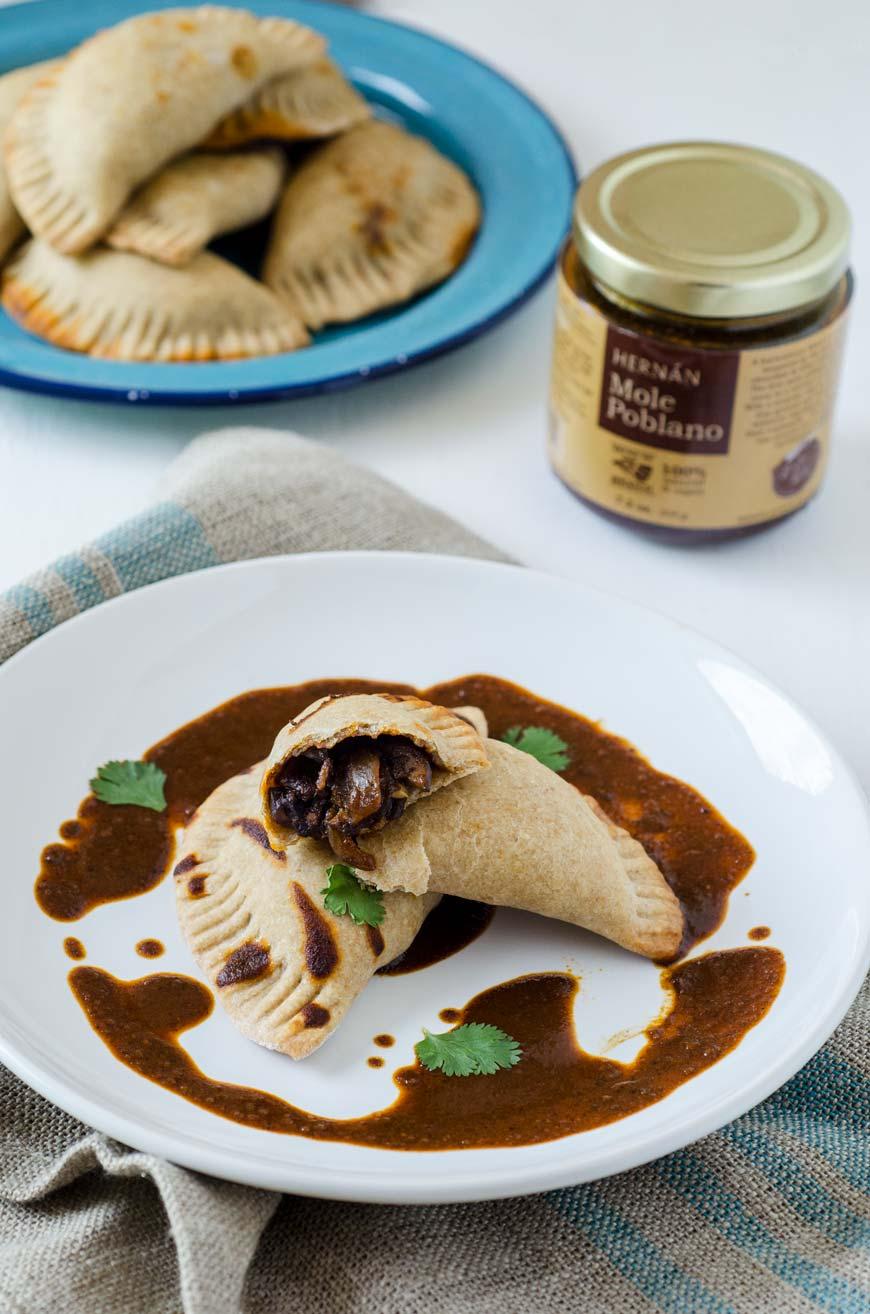 vegan empanadas on a white plate with hernan mole