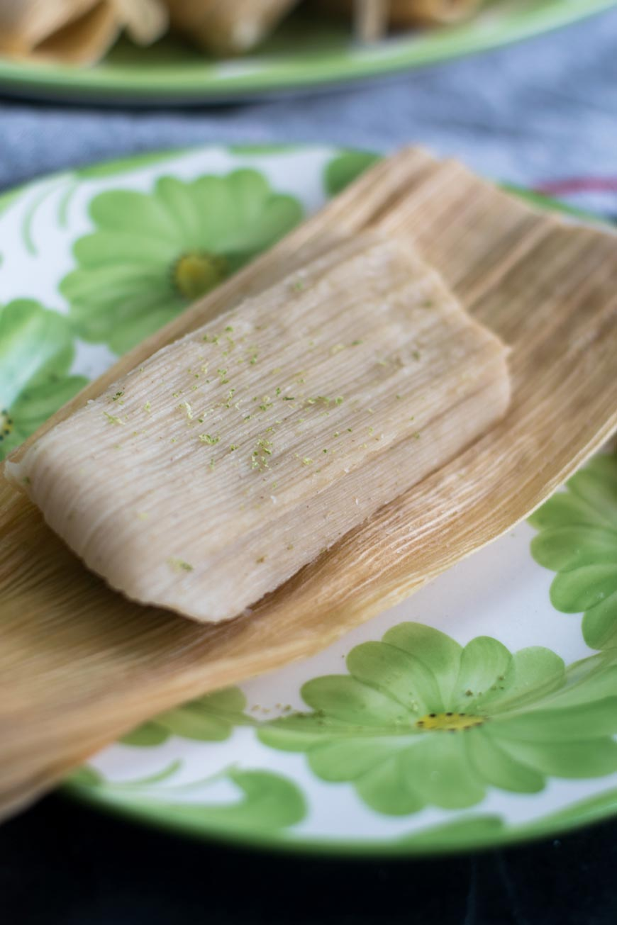 a lime tamal on a white and green plate
