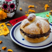 Vegan pan de muerto filled with chocolate surrounded by marigolds and a colorful skull