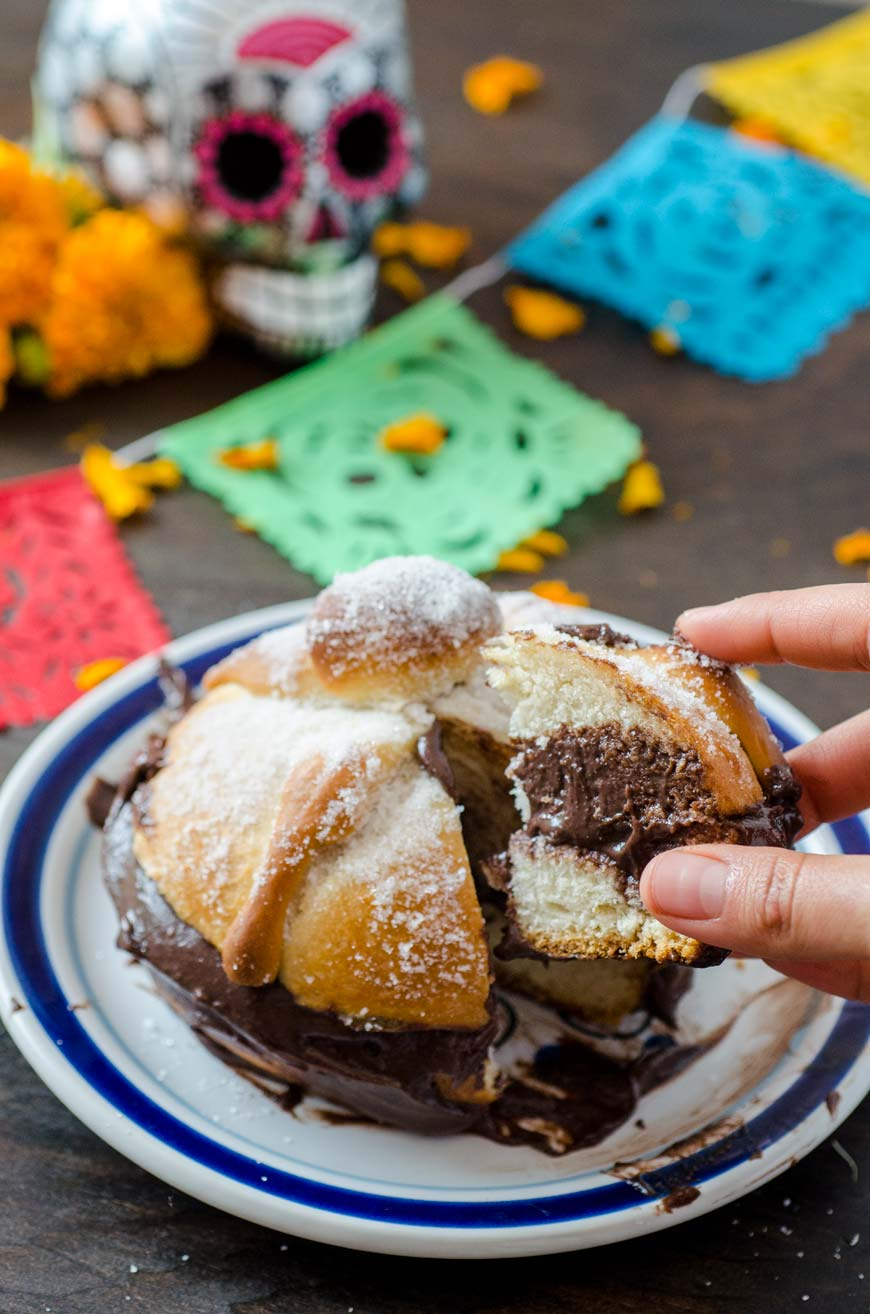 Vegan pan de muerto filled with chocolate, a hand is reaching in to take a piece