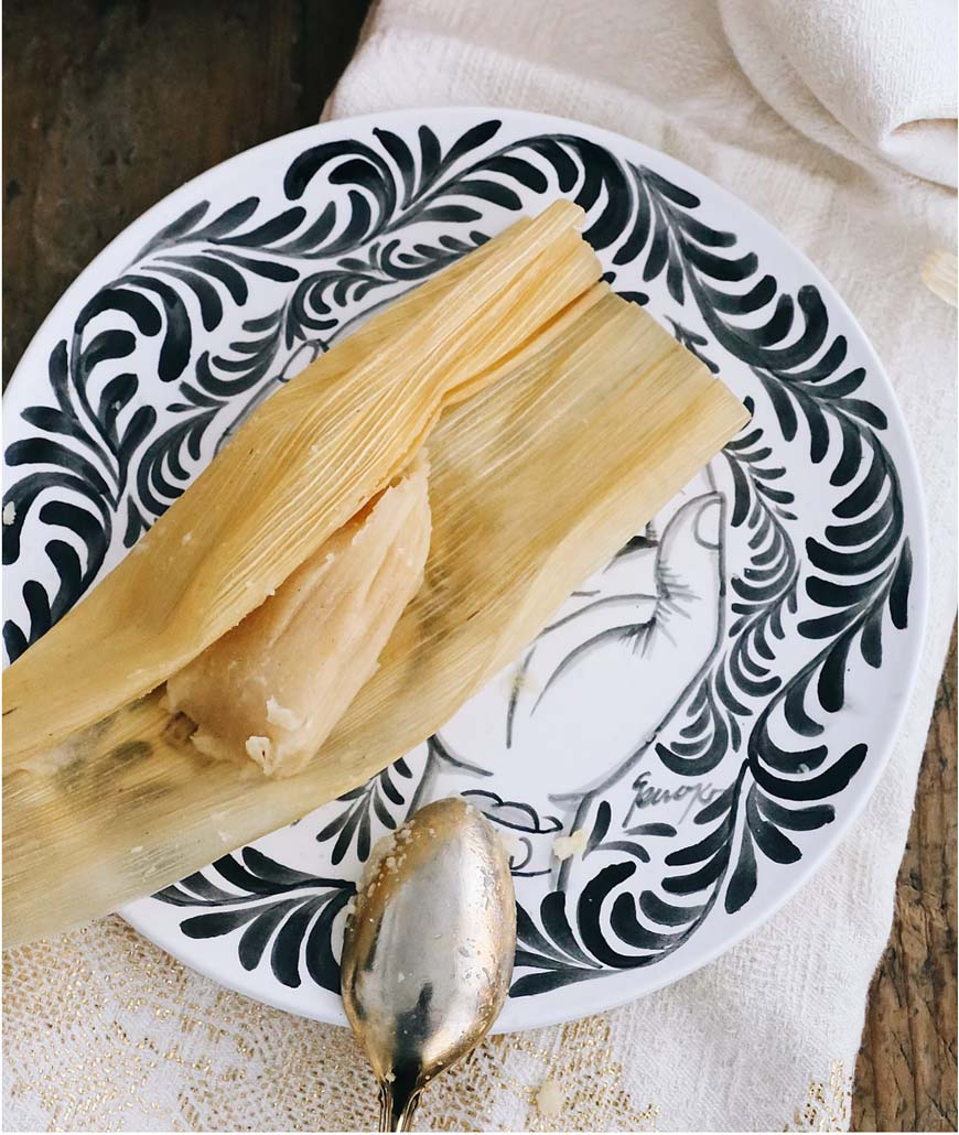 Pineapple tamal on a black and white plate with a silver spoon