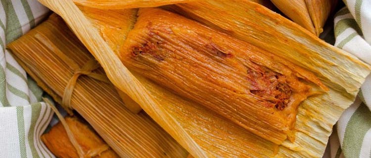 Red chile jackfruit tamales in a white and green tea towel