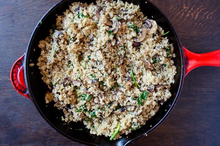 cooked quinoa and mushrooms in a saute pan