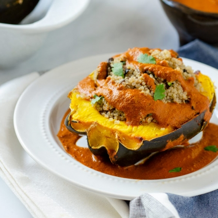 quinoa stuffed acorn squash with pipian rojo on a white plate