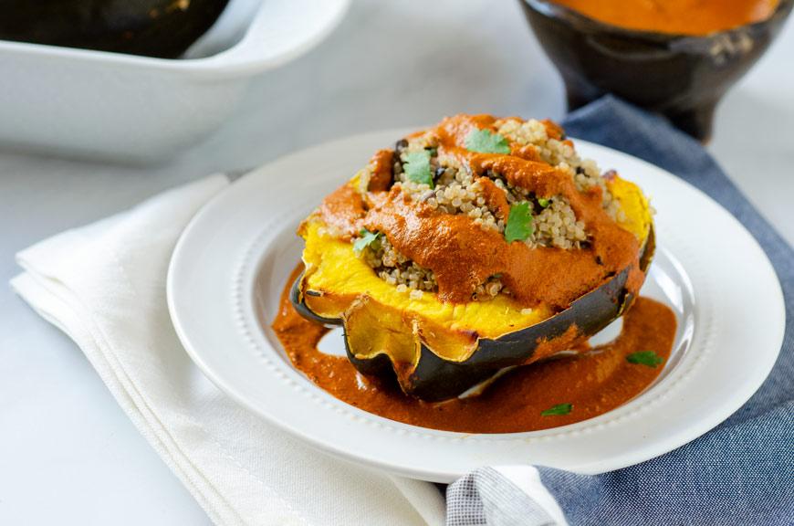 quinoa stuffed acorn squash with pipian rojo on a white plate
