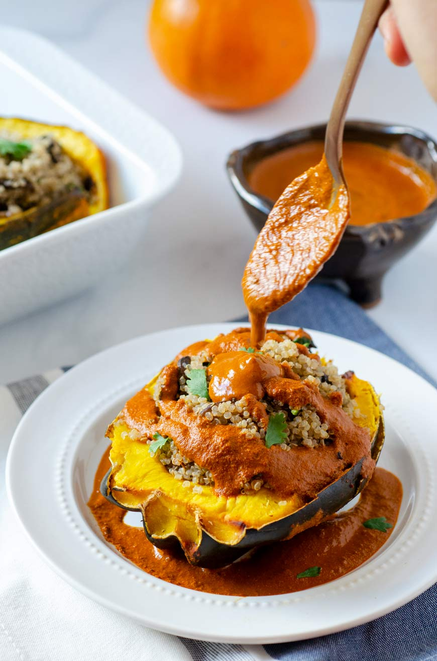 quinoa stuffed acorn squash and spoon pouring sauce on top of it
