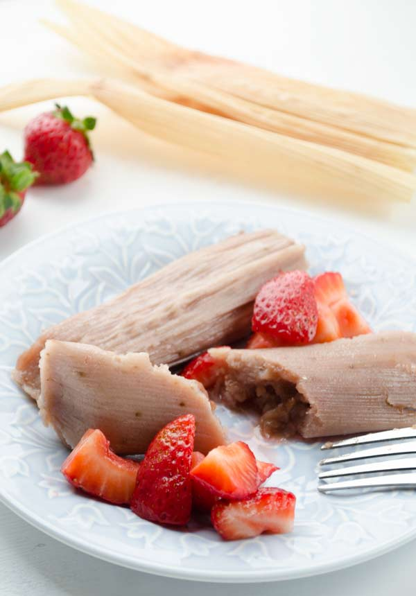 A pink tamal surrounded by strawberries on a blue plate.