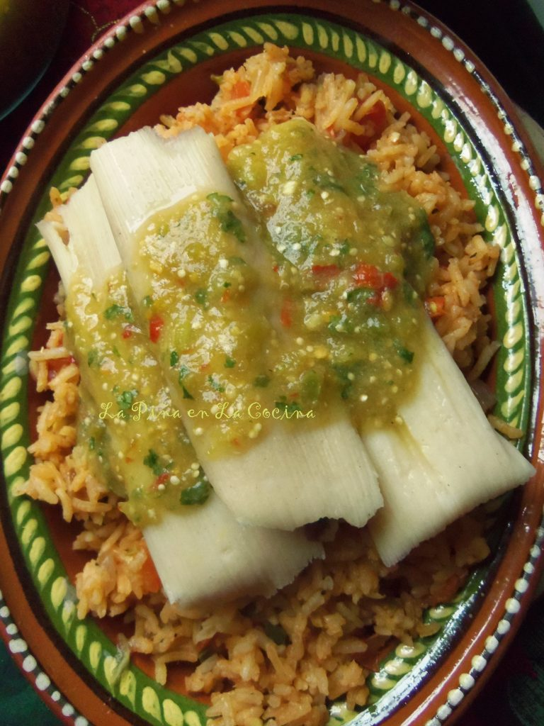 Three tamales topped with salsa verde over Mexican rice.
