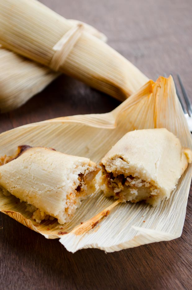 Two vegan tamales on a wooden board, one cut open
