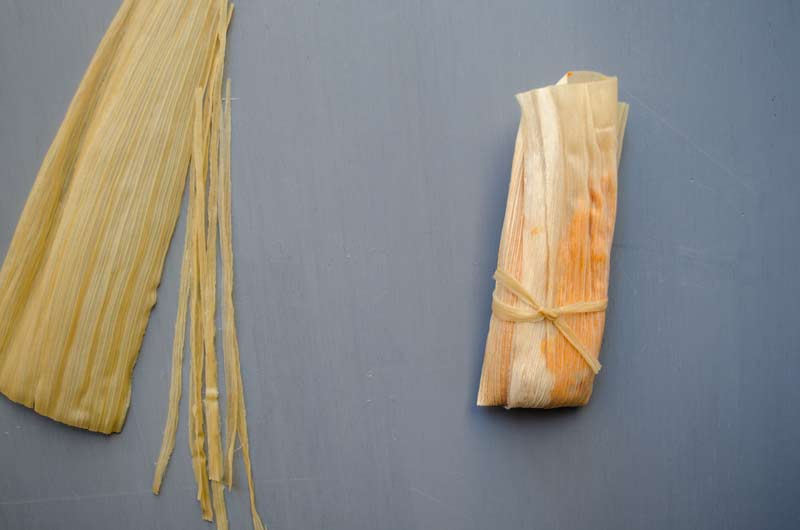 Tamales wrapped in corn husk on a blue back ground