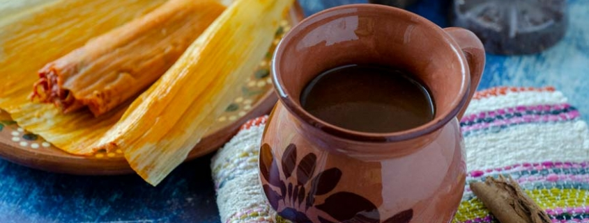 A mug of champurrado on a colored towel and a tamal beside it