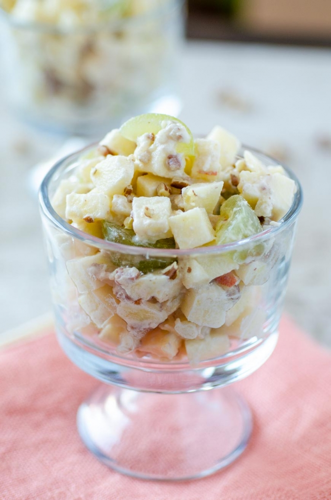 Mexican Christmas Apple Salad in a glass cup on top of a peach colored napkin