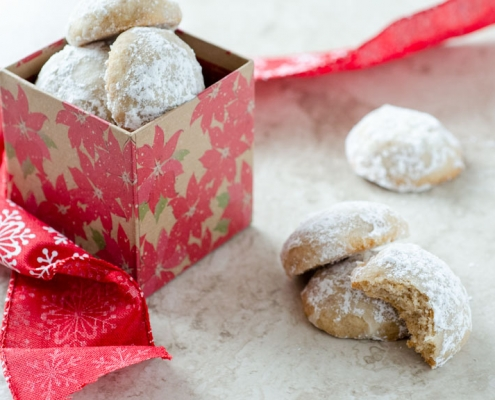vegan mexican wedding cookies in a poinsetta box with a ribbon