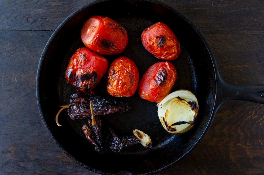 Roasted tomatoes, onion, dried peppers, and garlic in a cast iron pan