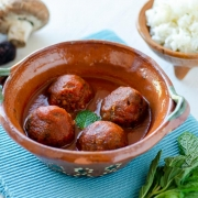 4 vegan meatballs in a clay bowl on a blue kitchen towel
